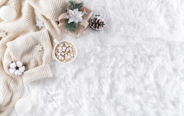 Zimowe przytulne tło z filiżanką kawy, ciepły sweter, pudełko, kwiat bawełny i bombka