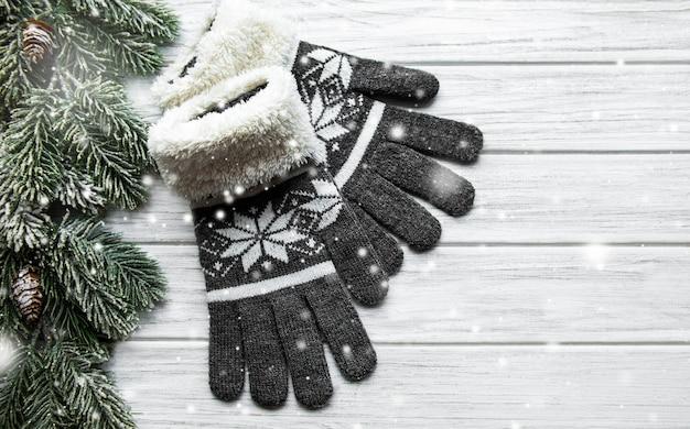 Zimowe rękawiczki dziane na drewnianej powierzchni w pobliżu gałęzi jodłowych