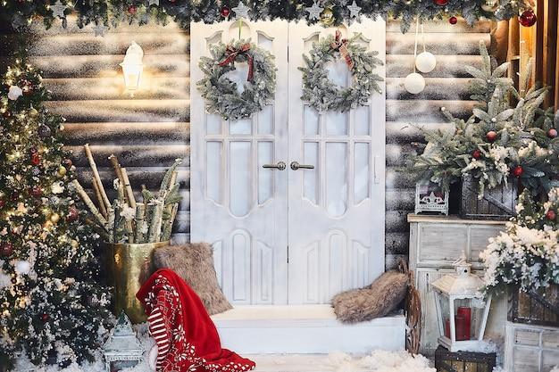 Zimowe rustykalne wnętrze udekorowane na nowy rok sztucznym śniegiem i choinką. zimowa fasada wiejskiego domu z dekoracjami świątecznymi w stylu rustykalnym.