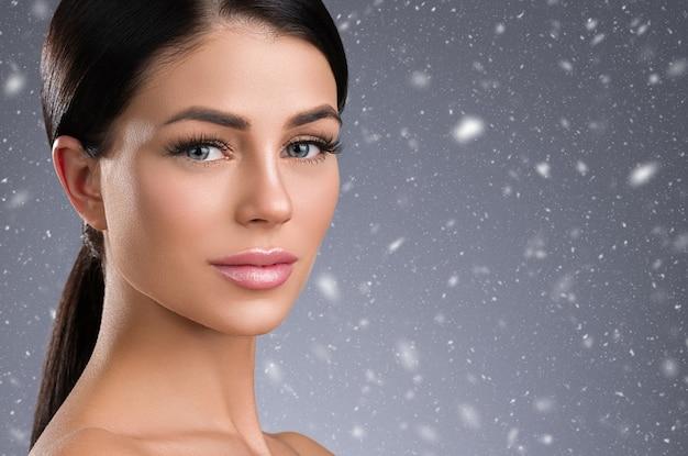 Zimowe rzęsy przedłużanie oczu kobiety z bliska płatki śniegu. strzał studio.