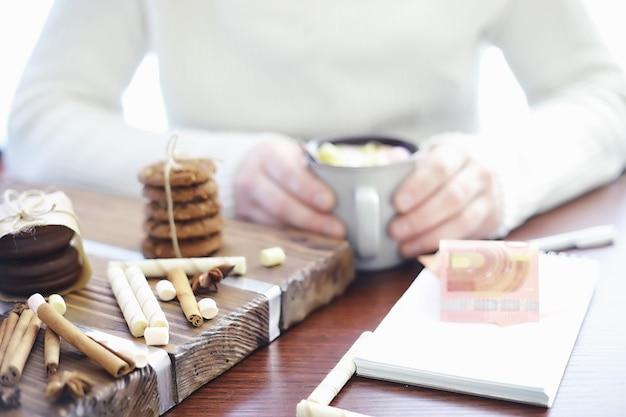 Zimowe śniadanie. kubek gorącej czekolady z piankami marshmallow i świeżo upieczonymi ciasteczkami. piernikowe ciastko i kawa.