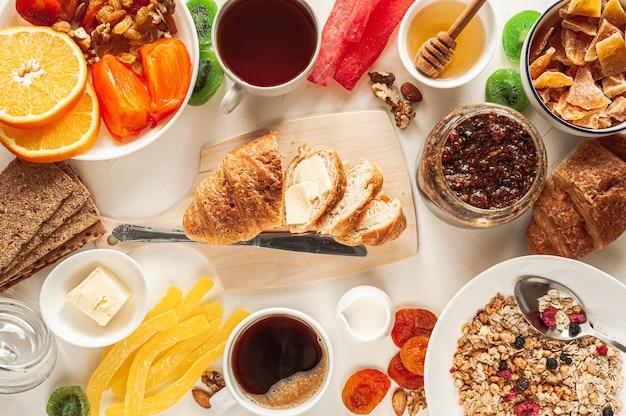 Zimowe śniadanie witaminowe na białym stole. śniadanie dla dwóch osób z granolą, owocami i bakaliami. wspaniałe śniadanie. bardzo szeroki baner. wysokiej jakości zdjęcie
