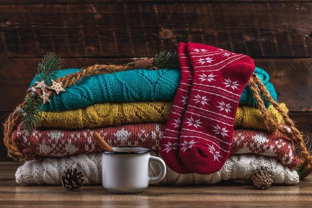 Zimowe swetry z dzianiny, ciepłe, świąteczne skarpety i kubek gorącego kakao na drewnianym tle. ubrania zimowe.