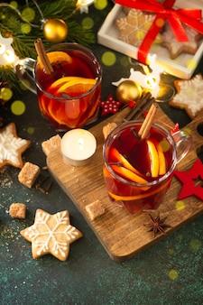 Zimowe świąteczne grzane wino z pomarańczą i przyprawami na świątecznym stole. skopiuj miejsce.