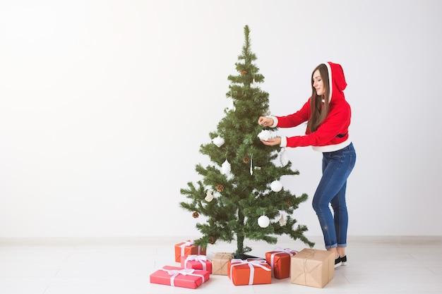 Zimowe święta bożego narodzenia i koncepcja ludzi piękna młoda kobieta dekorująca choinkę na biało