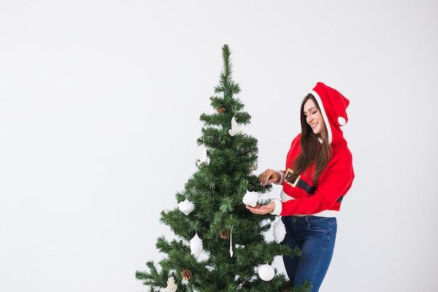 Zimowe święta bożego narodzenia i koncepcja ludzi portret pięknej młodej kobiety w santa hat dekorowanie