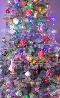 Zimowe tło bożonarodzeniowe: choinka ozdobiona błyszczącymi kulkami i szyszkami