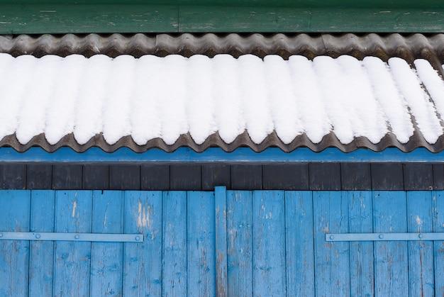 Zimowe tło dla projektu. streszczenie geometryczny fragment starej architektury. niebieskie bramy i łupkowy dach w śniegu