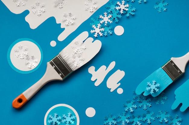 Zimowe tło w kolorze niebieskim i białym z pędzlem malarskim załadowane papierowymi płatkami śniegu