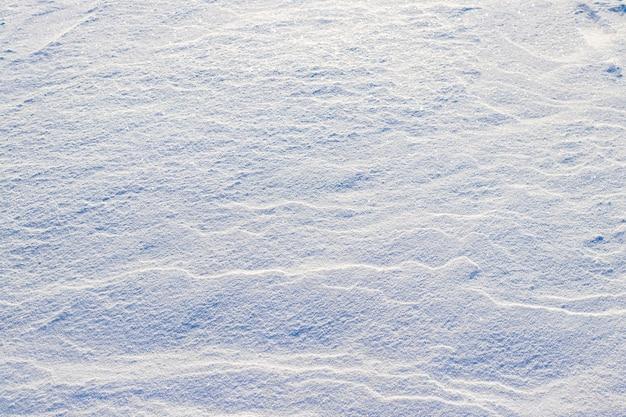 Zimowe tło z pokryte śniegiem ziemi po zamieci. śnieg na ziemi przy słonecznej pogodzie