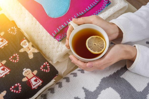 Zimowe ubrania o tradycyjnym designie, gorąca herbata z cytryną