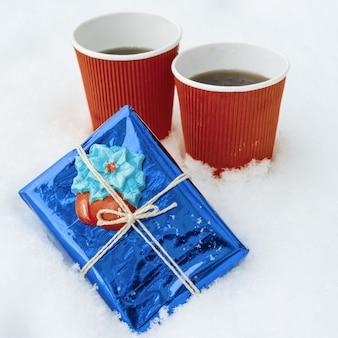 Zimowe wakacje czas śnieg tło prezent dwie filiżanki kawy