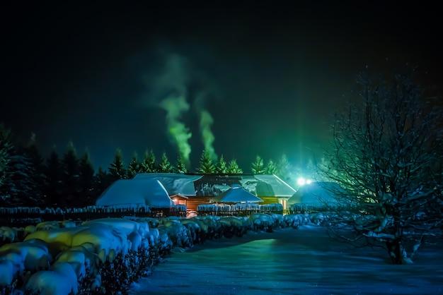 Zimowe zdjęcie nocne z domem w zaśnieżonej wiosce