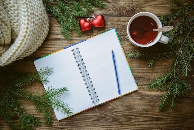 Zimowe zdjęcie świąteczne: notatnik z długopisem, filiżanka herbaty, gałązki jodły, zabawkowe serca i szalik