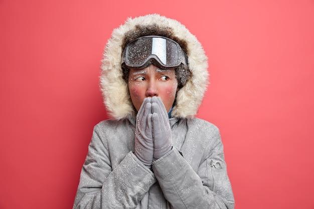 Zimowe zdjęcie zamarzniętej etnicznej kobiety rozgrzewa marznące ręce dmuchaniem gorącego powietrza, zimne w mroźny dzień, ubrana w ciepły płaszcz, aktywnie wypoczywa, nosi gogle narciarskie.