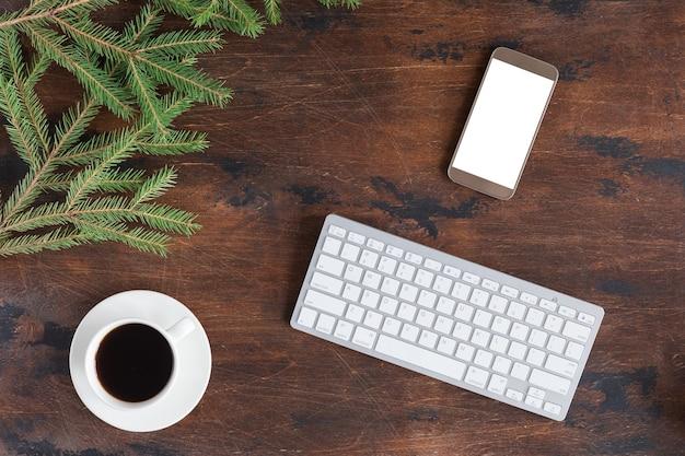 Zimowe zielone gałęzie jodły z filiżanką herbaty, telefonem komórkowym i białą klawiaturą komputerową na drewnianym tle, płasko leżące i widok z góry
