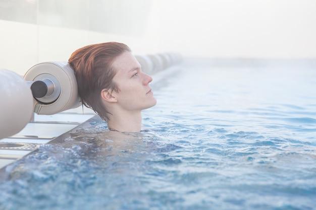 Zimowy basen z młodą atrakcyjną relaksującą kobietą.