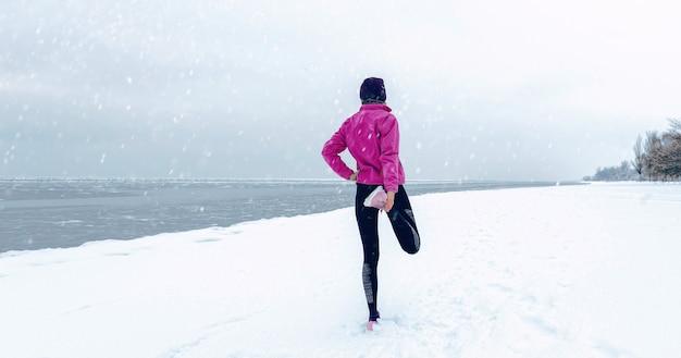 Zimowy bieg na zaśnieżonej plaży. pojęcie zdrowego stylu życia i sportu niezależnie od pogody i pory roku