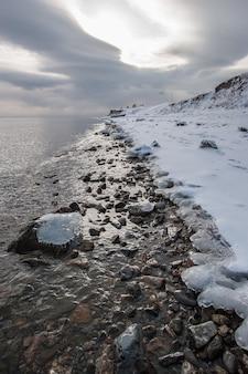 Zimowy brzeg jeziora bajkał z lodem na krawędzi wody i lodem na kamieniach w wodzie