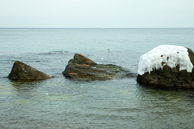 Zimowy brzeg morza z czystą wodą i dużymi kamieniami