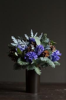 Zimowy bukiet gałązek jodłowych nobil, niebieskie hiacynty i szyszki, koncepcja zimowego prezentu