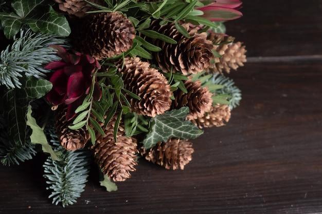 Zimowy bukiet gałązek jodłowych nobil, szyszek, pistacji, leucodendronu i bluszczu, koncepcja zimowego prezentu