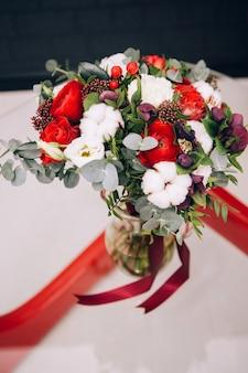 Zimowy bukiet z czerwonych róż, bawełny, eukaliptusa. bukiet z czerwoną wstążką. czerwony ranunculus