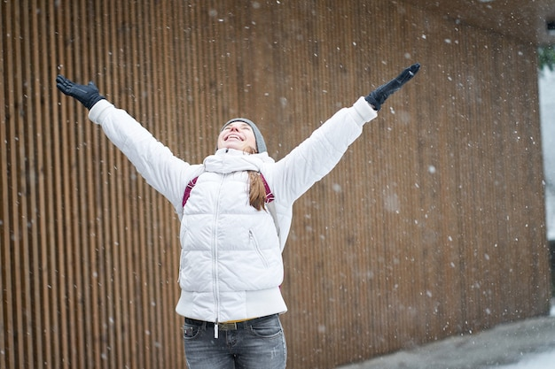 Zimowy czas. młoda szczęśliwa kaukaski dziewczyna ubrana w białą kurtkę, ciesząc się pierwszym śniegiem z podniesionymi rękami.