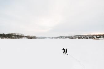 Zimowy. Facet i dziewczyna udają się na pokryte śniegiem zimowe, zamarznięte jezioro.