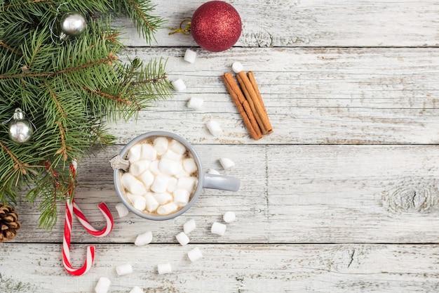 Zimowy gorący napój. świąteczna gorąca czekolada lub kakao z ptasie mleczko na białym drewnianym stole z dekoracjami świątecznymi