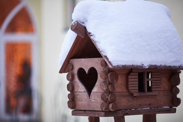 Zimowy karmnik dla ptaków wykonany z drewna. śnieg na dachu