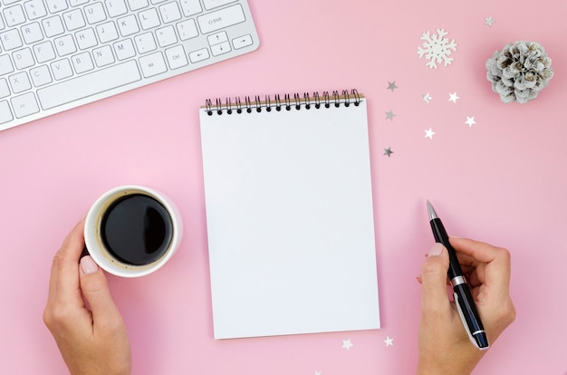 Zimowy kobiecy widok z góry makieta miejsca pracy z notatnikiem i rękami, klawiaturą i dekoracją świąteczną