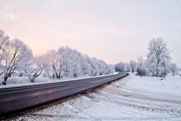 Zimowy krajobraz. asfaltowana wiejska droga o wczesnym, zimnym wschodzie słońca