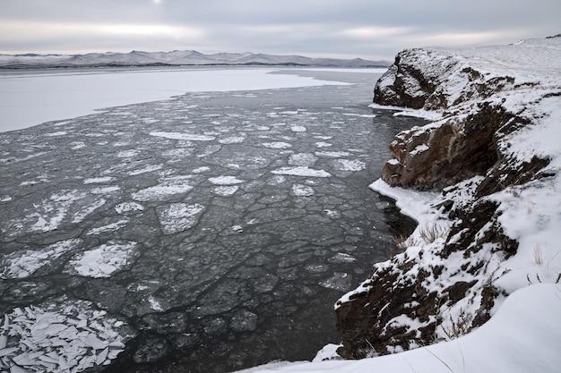 Zimowy krajobraz, dryfujące kry lodowe otoczone skałami