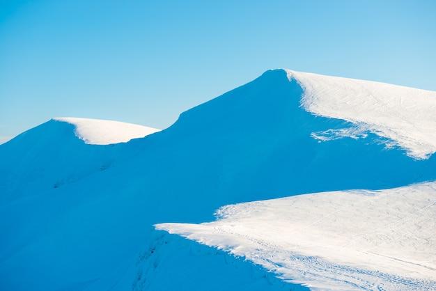 Zimowy krajobraz gór z świecącym słońcem na jasnym błękitnym niebie