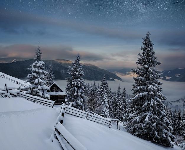 Zimowy krajobraz. górska wioska w ukraińskich karpatach. wibrujące nocne niebo z gwiazdami, mgławicą i galaktyką. astrofotografia głębokiego nieba.