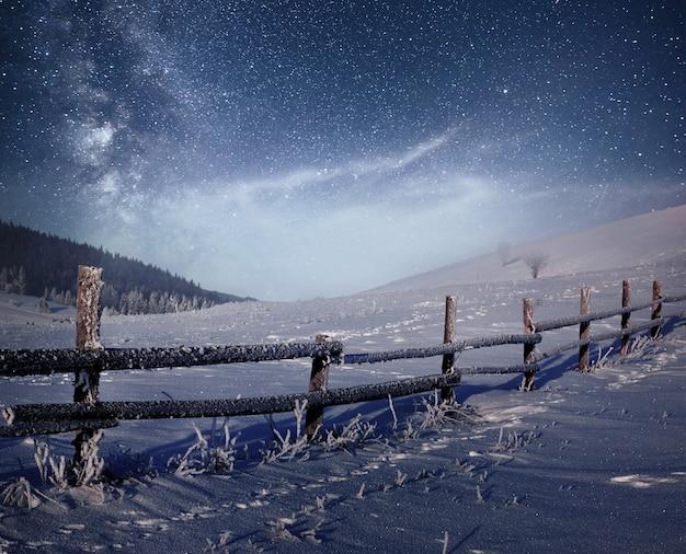 Zimowy krajobraz. górska wioska w ukraińskich karpatach. wibrujące nocne niebo z gwiazdami, mgławicą i galaktyką. astrofotografia z głębokiego nieba