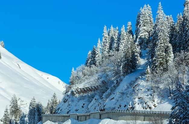 Zimowy krajobraz górski z śnieżną jodłą i drogą na zboczu (austria, tyrol).