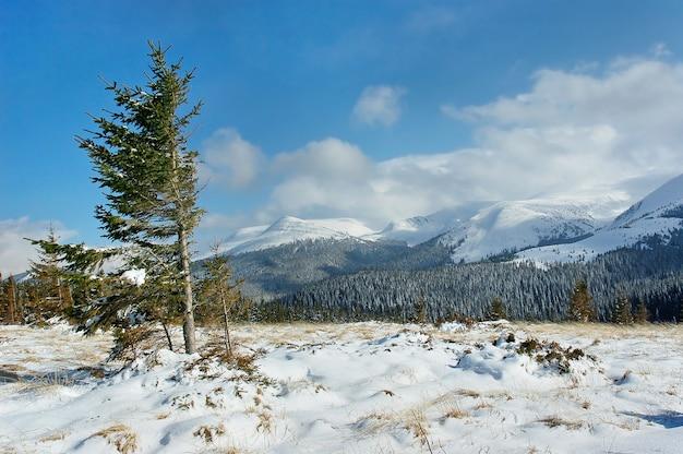 Zimowy krajobraz górski ze śniegiem i błękitne niebo z chmurami dominujące wiatry w górach