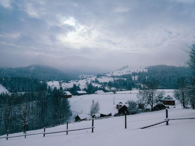 Zimowy krajobraz górskiej wioski z drewnianymi domami