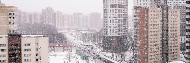 Zimowy krajobraz miasta z padającego śniegu. widok na miasto z wysokości. zamieć na ulicy z płatkami śniegu. budynki mieszkalne i droga z jeżdżącymi samochodami. transparent