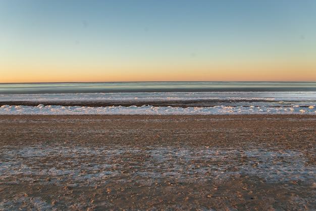 Zimowy krajobraz na plaży, wybrzeże z pękniętym lodem i otwartą wodą morską.