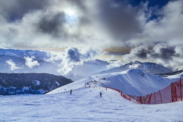 Zimowy krajobraz, niebo z chmurami, stoki narciarskie ze śniegiem w ośrodku narciarskim rosa khutor w rosji. cudowny widok na góry kaukazu.