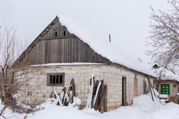 Zimowy krajobraz wsi, zrujnowany opuszczony zniszczony budynek pokryty śniegiem.