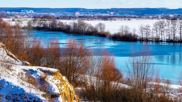 Zimowy krajobraz z drzewami i skałami nad rzeką przy słonecznej pogodzie