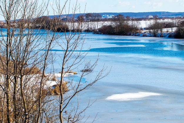 Zimowy krajobraz z drzewami nad rzeką przy słonecznej pogodzie
