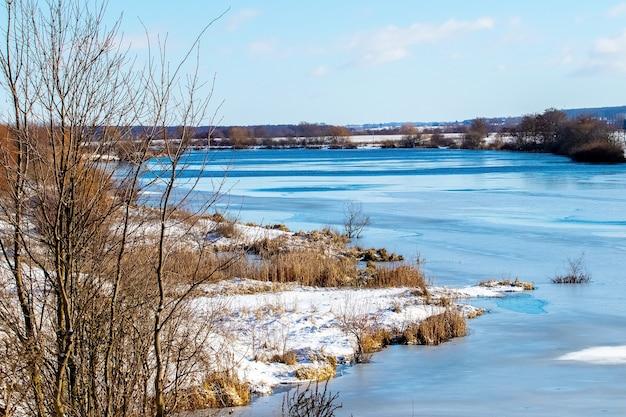 Zimowy krajobraz z lasem nad rzeką