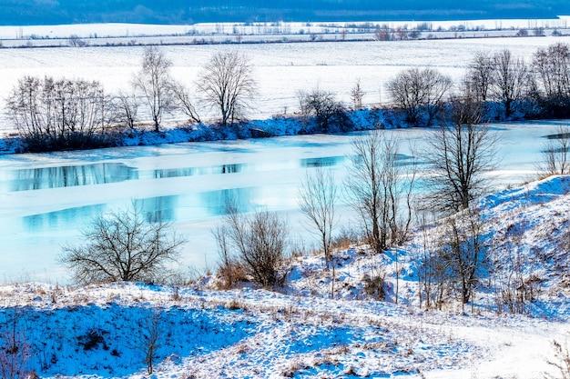 Zimowy krajobraz z rzeką i drzewami nad rzeką w słoneczny dzień