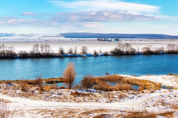 Zimowy krajobraz z rzeką i pokrytą śniegiem trawą nad rzeką