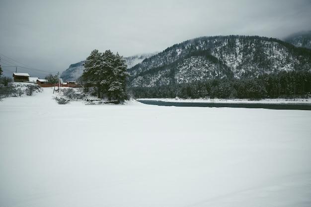 Zimowy krajobraz z wioską w górach na brzegu górskiej rzeki. mroźny, mglisty dzień. morochrome.